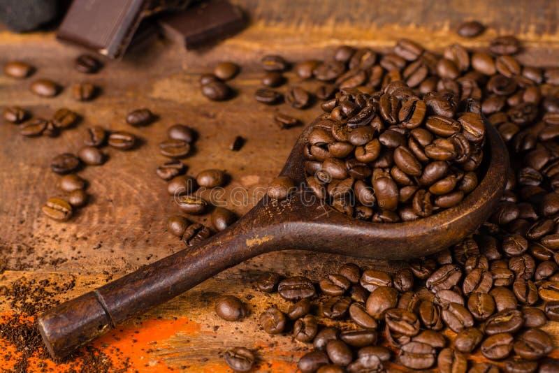 A obscuridade roasted feijões de café puros da goma-arábica e o coffe à terra no w foto de stock