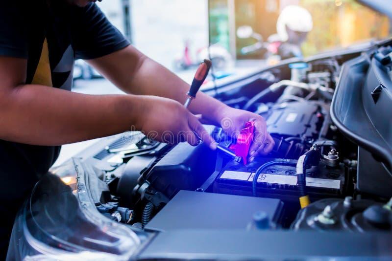 Obscuro da bateria de carro em mudança do mecânico masculino, bateria de carro da fixação do coordenador do mecânico imagens de stock royalty free