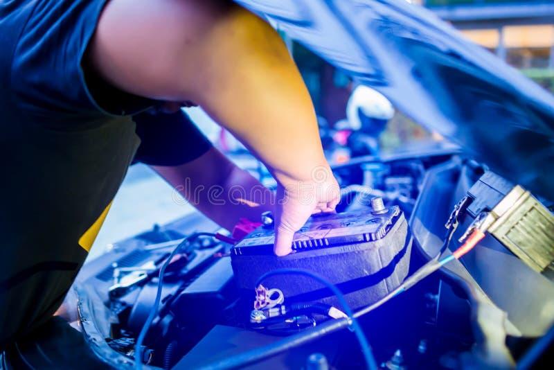 Obscuro da bateria de carro em mudança do mecânico masculino, bateria de carro da fixação do coordenador do mecânico imagem de stock