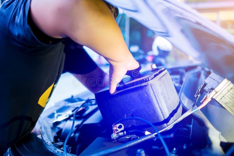 Obscuro da bateria de carro em mudança do mecânico masculino, bateria de carro da fixação do coordenador do mecânico foto de stock