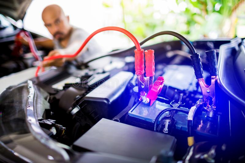 Obscuro da bateria de carro em mudança do mecânico masculino, da bateria de carro da fixação do coordenador do mecânico com  imagem de stock royalty free
