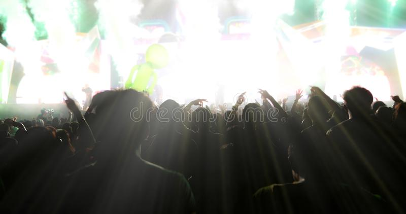 Obscuro das silhuetas da multidão do concerto na ideia traseira do festival fotos de stock