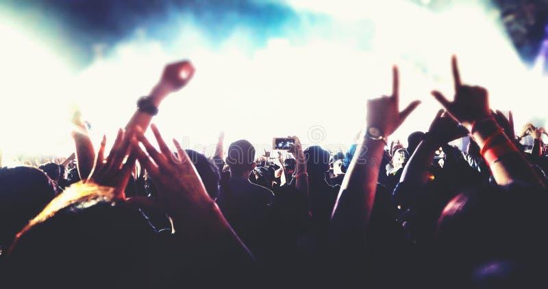 Obscuro das silhuetas da multidão do concerto na opinião traseira a multidão do festival levantar suas mãos na fase brilhante ilu foto de stock