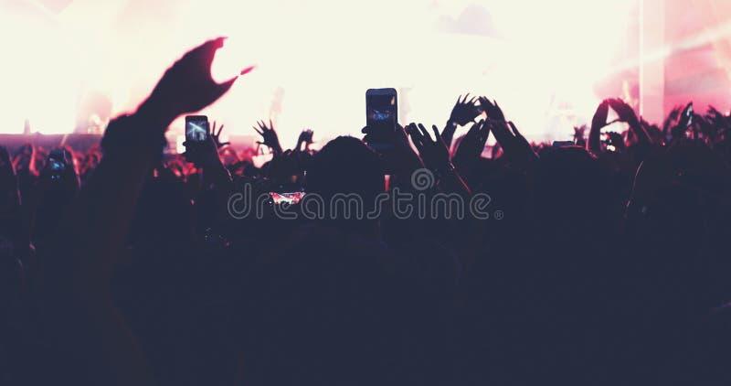 Obscuro das silhuetas da multidão do concerto na opinião traseira a multidão do festival levantar suas mãos na fase brilhante ilu fotografia de stock
