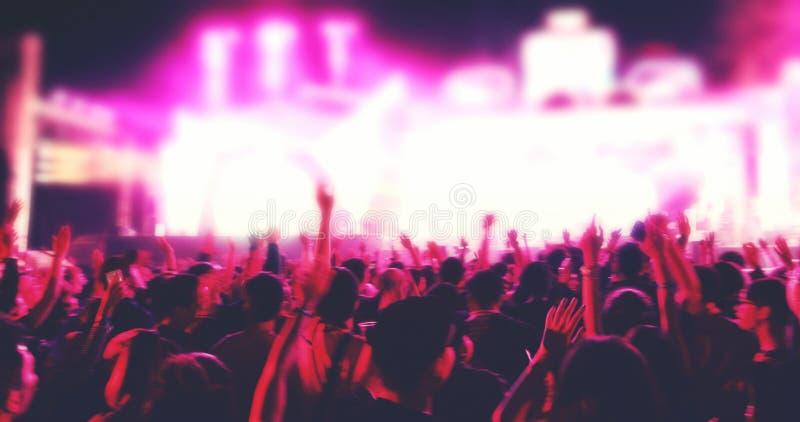 Obscuro das silhuetas da multidão do concerto na opinião traseira a multidão do festival levantar suas mãos na fase brilhante ilu imagens de stock
