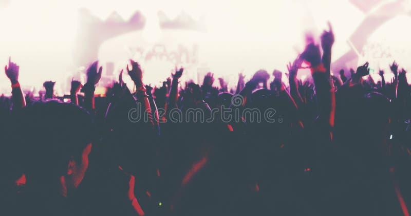 Obscuro das silhuetas da multidão do concerto na opinião traseira a multidão do festival levantar suas mãos na fase brilhante ilu fotos de stock
