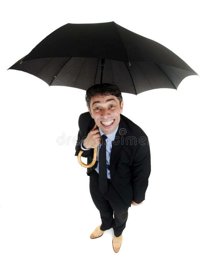 Obsequious businessman holding. Obsequious businessman sheltering under an umbrella looking up at the camera from underneath with a cheesy insincere smile, high stock photo