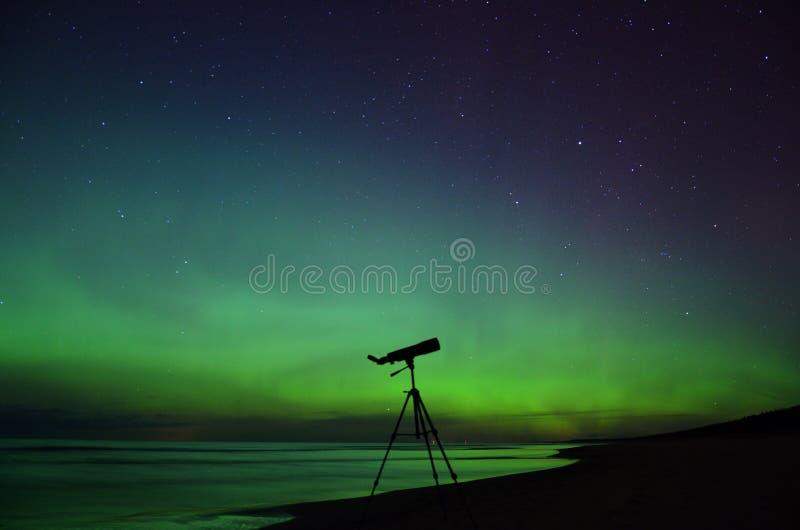 Observação das luzes polares e das estrelas do aurora borealis no telescópio foto de stock