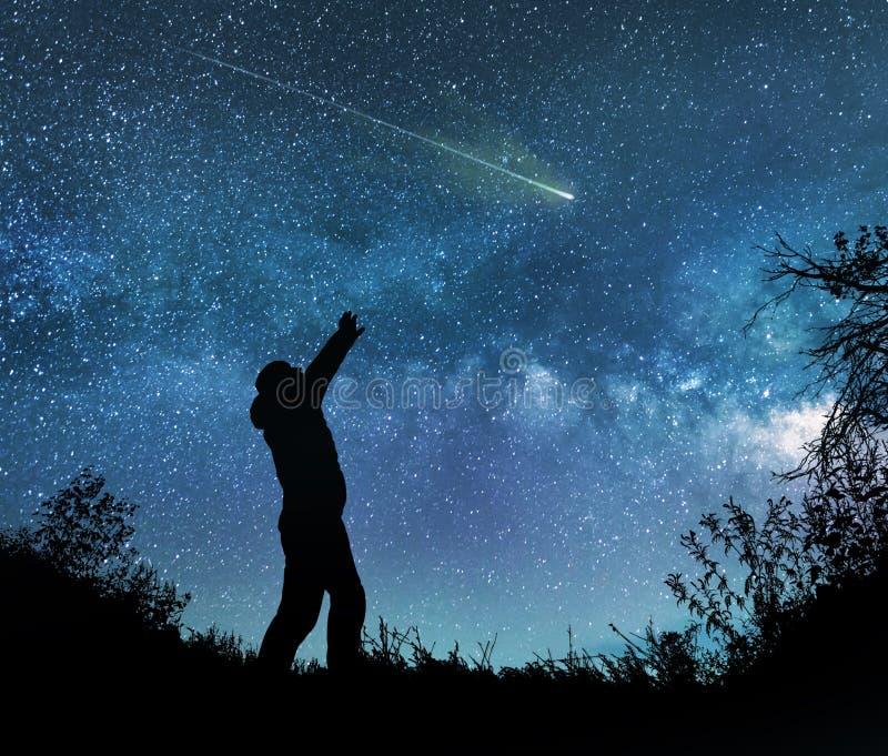 A observação do homem protagoniza no céu noturno foto de stock royalty free