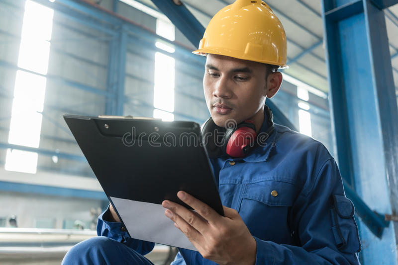 Observações asiáticas da escrita do trabalhador sobre a fabricação imagens de stock