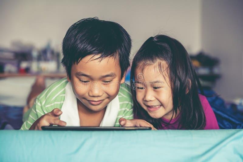 Observación asiática de los niños video y jugar al juego en la tableta digital fotos de archivo libres de regalías