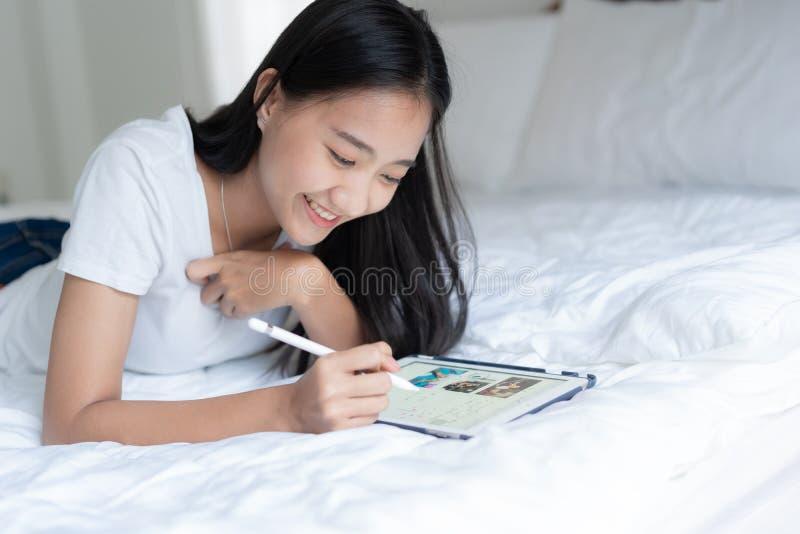 Observación asiática joven hermosa de la mujer social en línea La muchacha de Asia es diversión y feliz lindos en la cama en su h imágenes de archivo libres de regalías