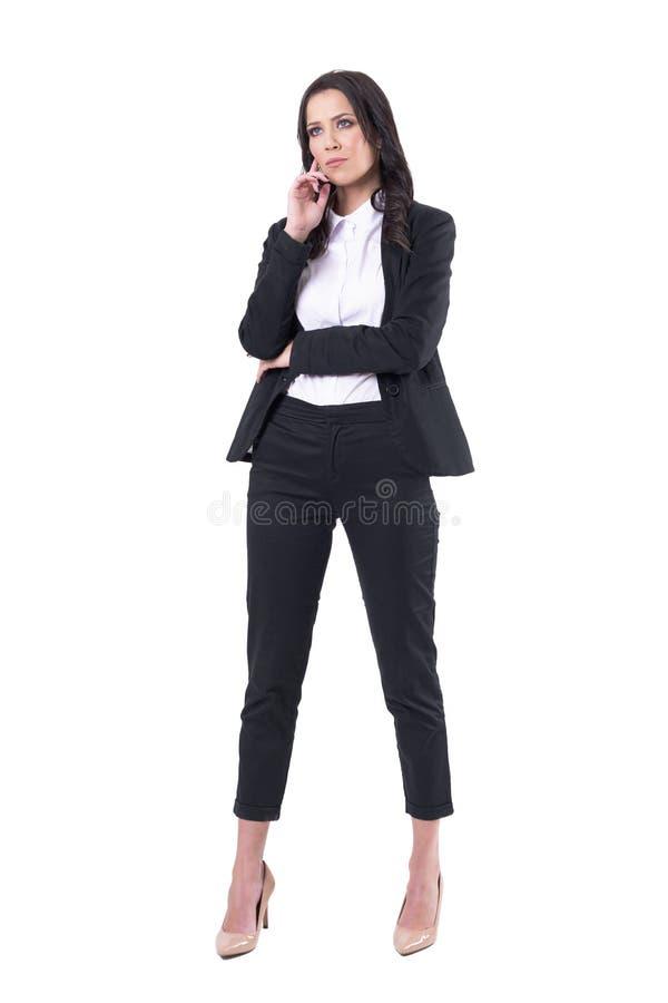 Observación confiada seria de la mujer de negocios interesada con la mano en la barbilla Concepto de la atención imagenes de archivo