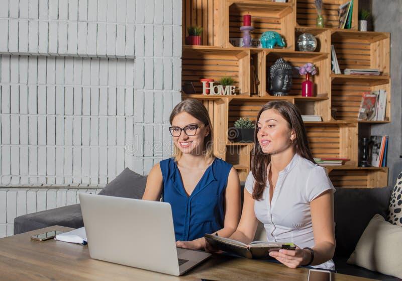 Observación de dos encargados de la mujer joven webinar en el ordenador portátil, sentándose en interior moderno imagenes de archivo