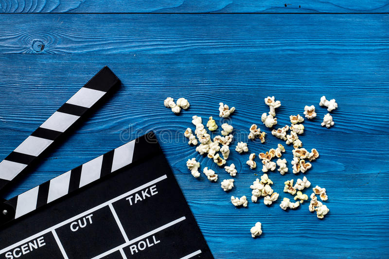 Observación de la película Clapperboard y palomitas de la película en copyspace de madera azul de la opinión superior del fondo d fotos de archivo