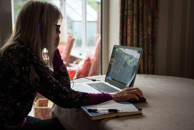 Observación independiente webinar en su ordenador portátil, auriculares que llevan de la mujer imagen de archivo libre de regalías