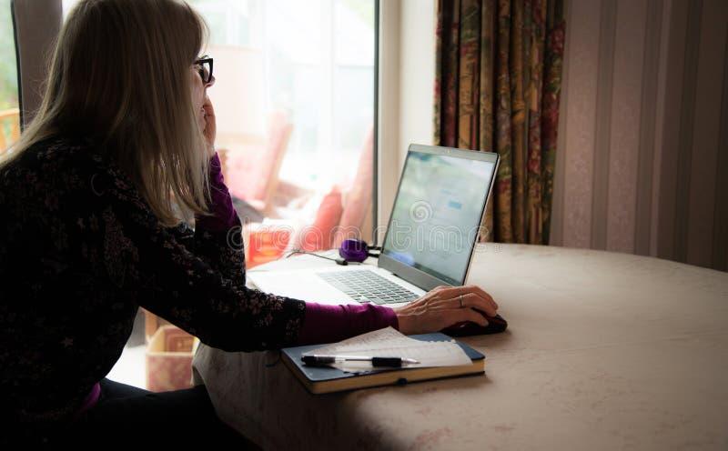 Observación independiente webinar en su ordenador portátil, auriculares que llevan de la secretaria de finanzas imágenes de archivo libres de regalías