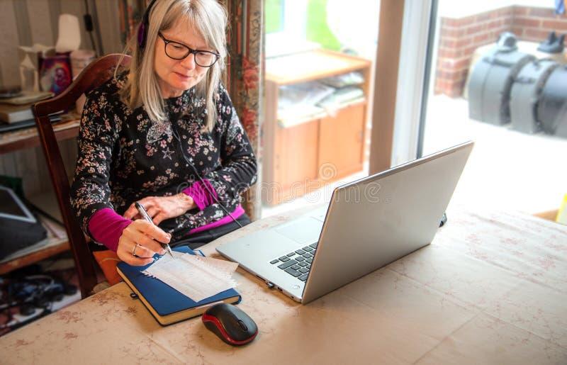Observación webinar en su ordenador portátil, auriculares que llevan de la mujer del nómada de Digitaces imágenes de archivo libres de regalías