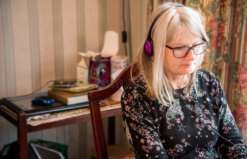 Observaci?n webinar en su ordenador port?til, auriculares que llevan de la mujer imagen de archivo libre de regalías
