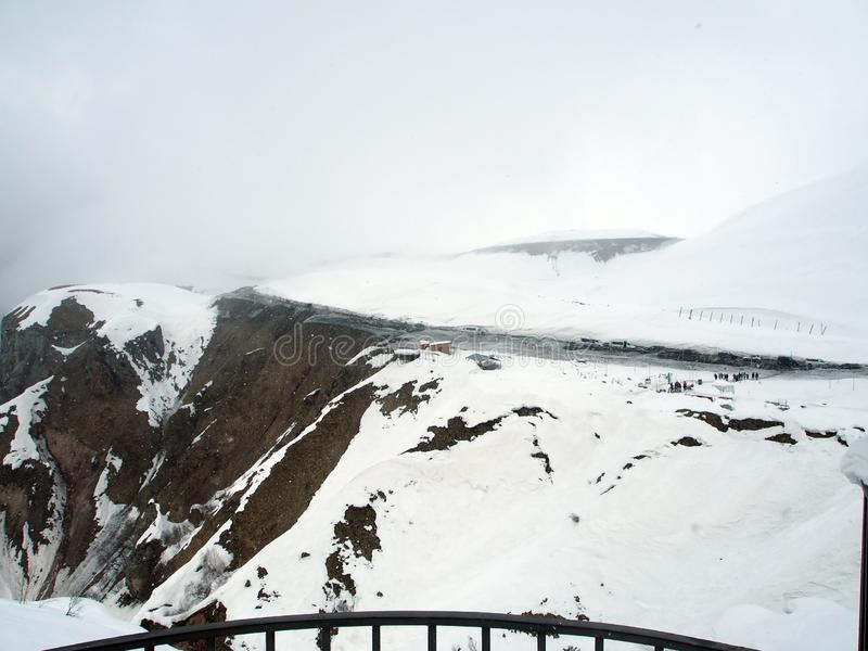 Observation deck for tourists along the Georgian military road in spring during heavy snowfall stock photos