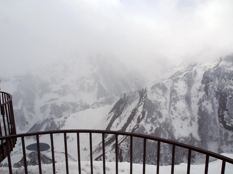 Observation deck for tourists along the Georgian military road in spring during heavy snowfall stock photography