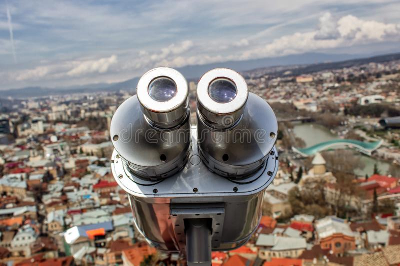 Observation deck and viewing binoculars close-up overlooking the city of Tbilisi. royalty free stock image