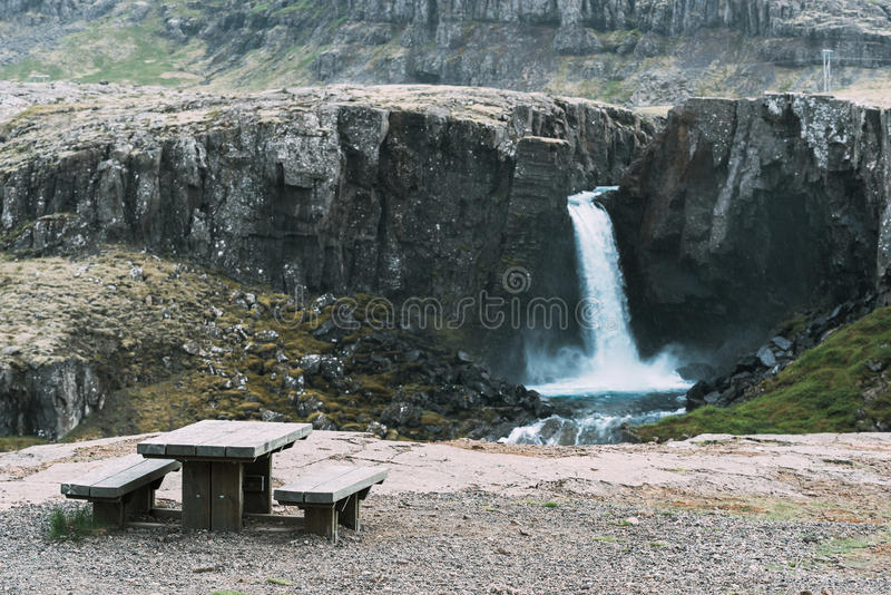 Observation deck with views of the beautiful waterfall in Iceland. Tourist observation deck with wooden table and bench. View of beautiful waterfall in the royalty free stock photography