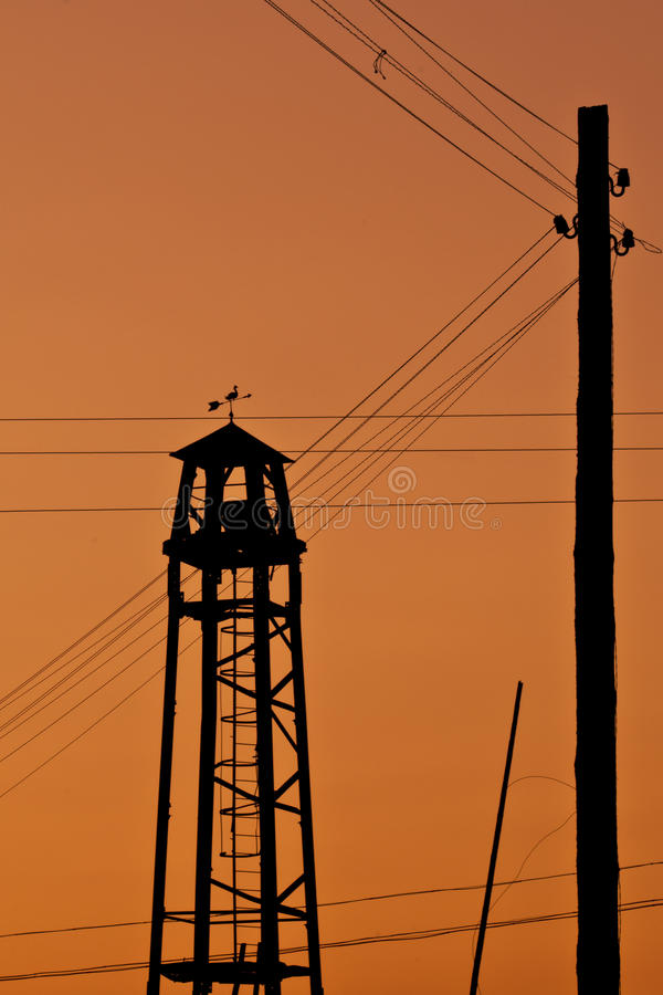 Observation fire tower on a backgraund of sunset. With wood pillar and electric power line stock photography