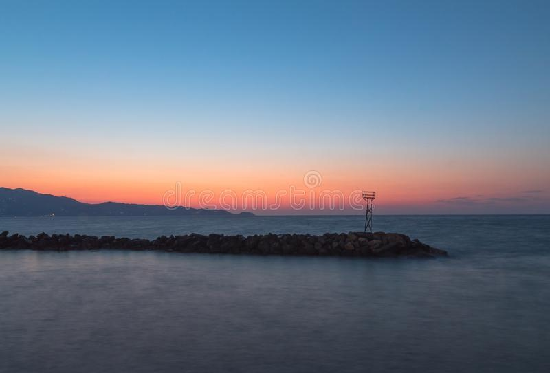 Observatorio oxidado viejo en el borde de los trituradores de onda en el puesta del sol foto de archivo
