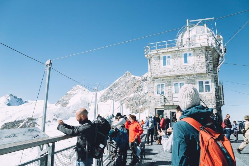 Observatorium för Jungfrau snöig bergtoppmöte och turistfolk i Schweiz arkivfoto