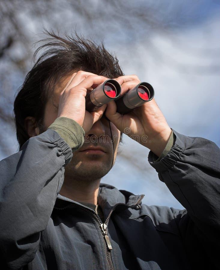 Observer. Man look through the binoculars royalty free stock photo