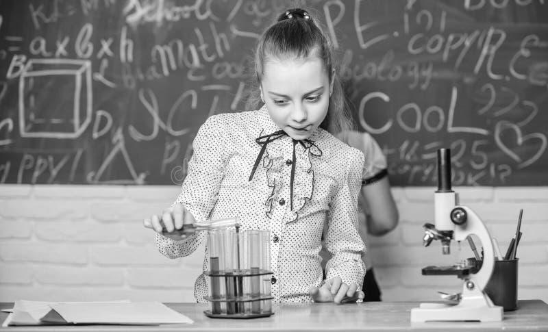 Observera kemiska reaktioner Kemisk reaktion som mycket ?r mer sp?nnande ?n teori Flickor som arbetar kemiskt experiment naturlig arkivfoton