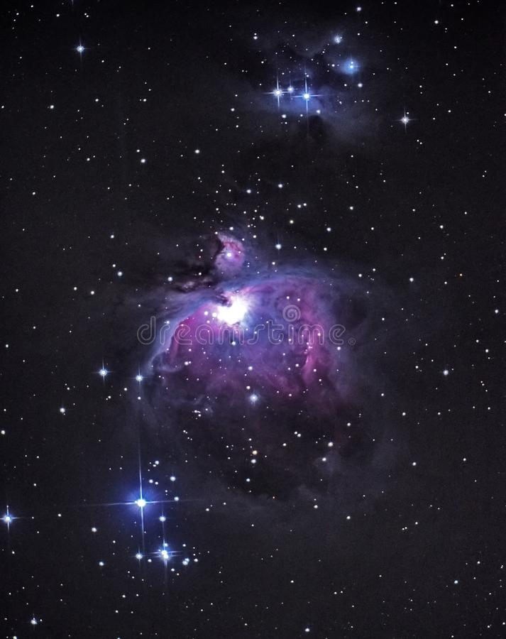 Observig de las estrellas del cielo nocturno sobre hombre de la constelación de Orión del telesocpe y la nebulosa de funcionamien imagenes de archivo