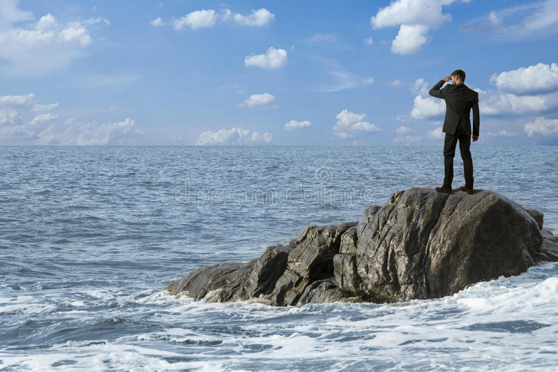 Observing man on rocks in the sea. Montage royalty free stock photography
