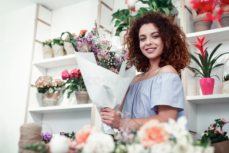 Proud curly beautiful woman showing her excellent bouquet stock photos