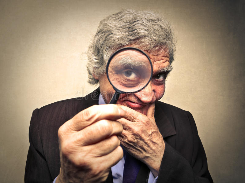 Observing very closely. Portrait of older man looking closely stock image