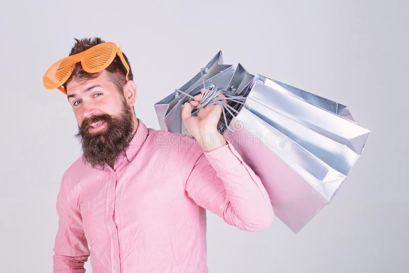Obsessed with shopping. Addicted consumer concept. Man carefree bearded hold shopping bags. Shopping dumb wasting money. Stupid things you do with your money stock images