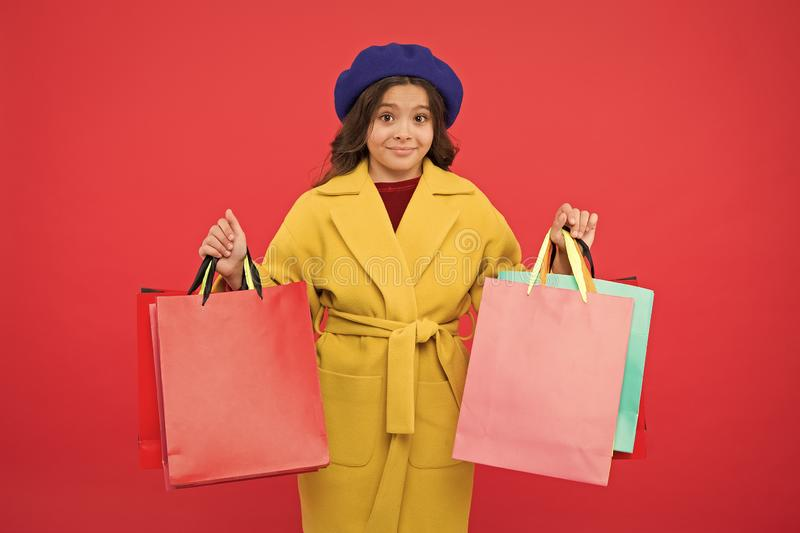 Obsessed with shopping. Girl cute kid hold shopping bags red background. Get discount shopping on birthday holiday stock images