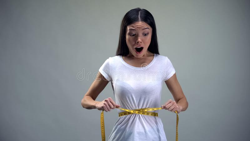 Obsessed woman tightening measuring tape on her waist desire to be slim, bulimia. Stock photo stock image