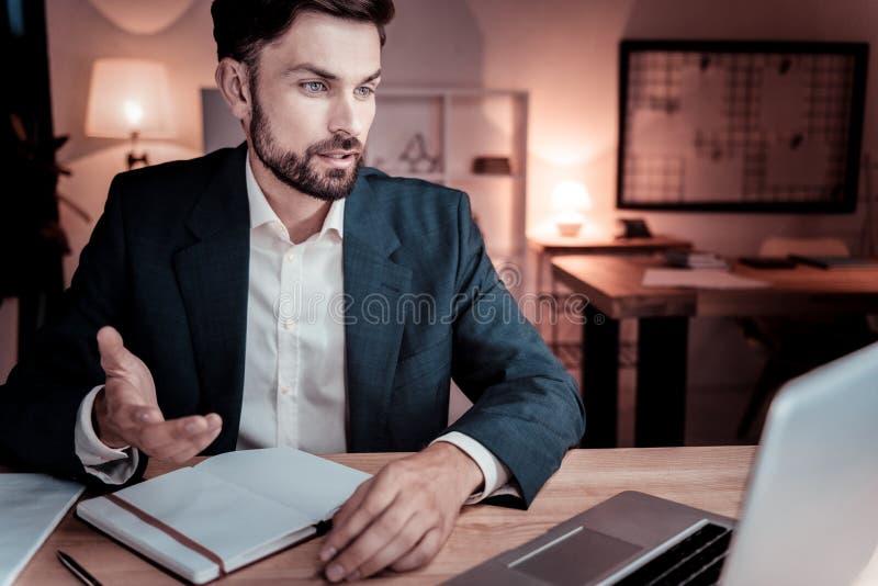 Obsiadły odpowiedzialny pracownik patrzeje komunikować i laptop zdjęcie royalty free