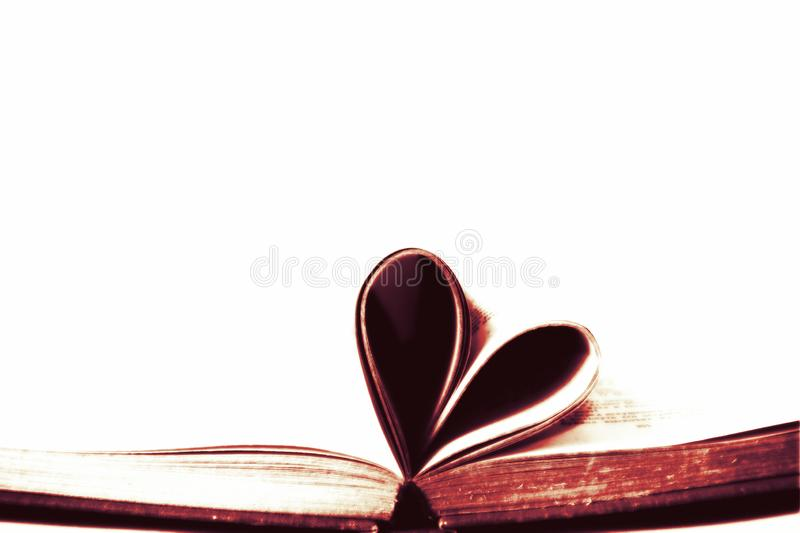 Obsolete old book with pages shaped into heart shape symbol with empty white isolated copy space background. Image stock photos