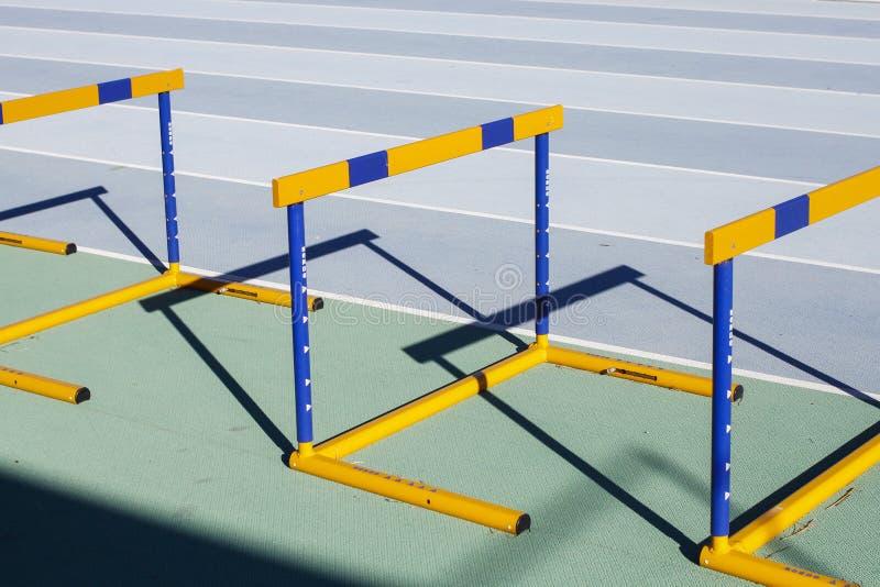 Obstáculos de salto azuis amarelos na pista de atletismo imagens de stock royalty free