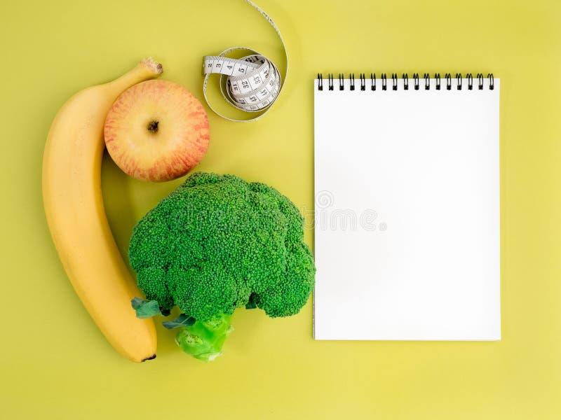 Obst und Gemüse - Apfel, Banane und Brokkoli auf hellem yel lizenzfreie stockfotografie