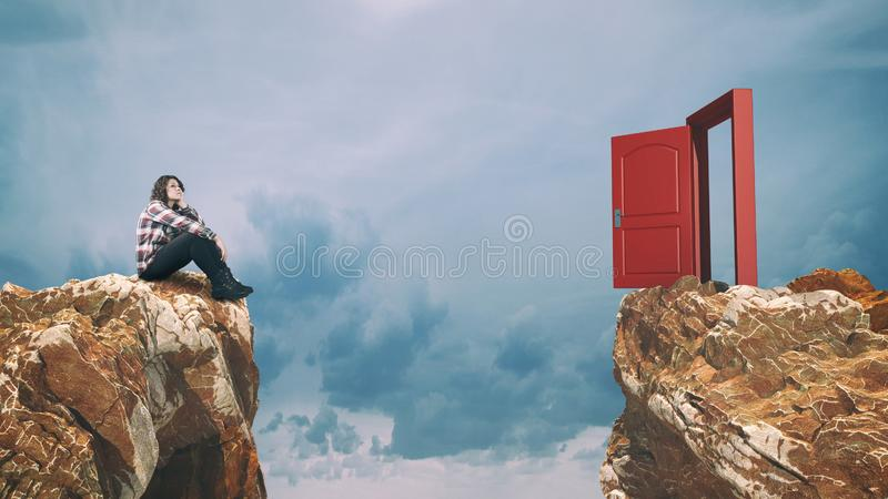 Obstacle door difficulty. Thoghtful woman sits on a moutain peak looking at a opened door over a gap stock photos
