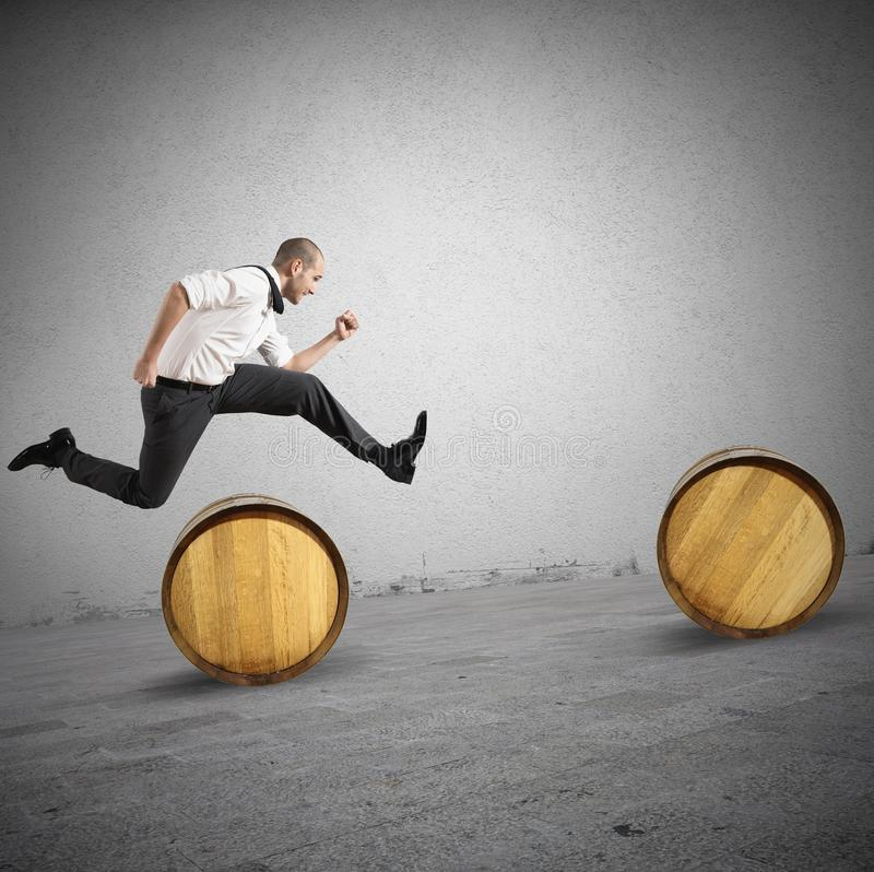 Obstacles. Concept of difficulty with businessman that jumps obstacles stock photography