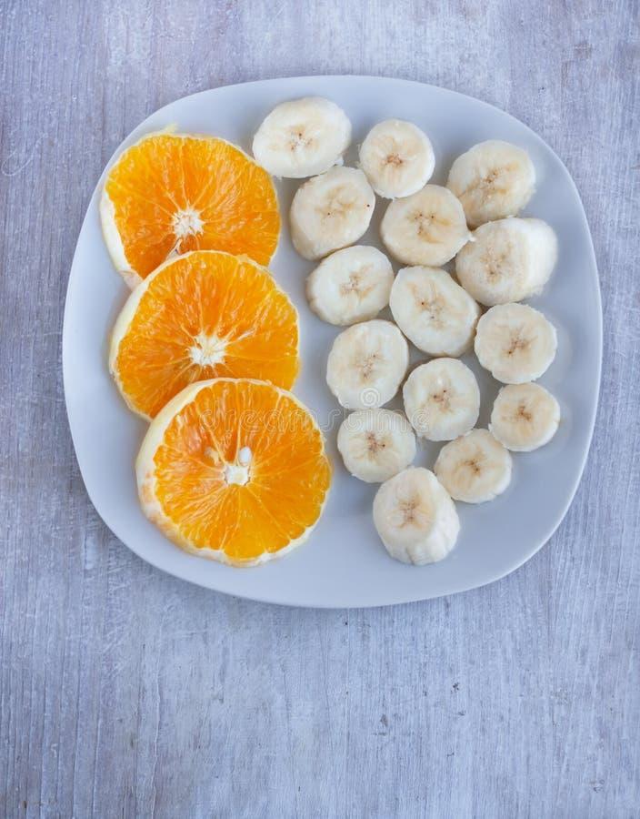 Obstbananen und Orange auf der Porzellanplatte stockbilder