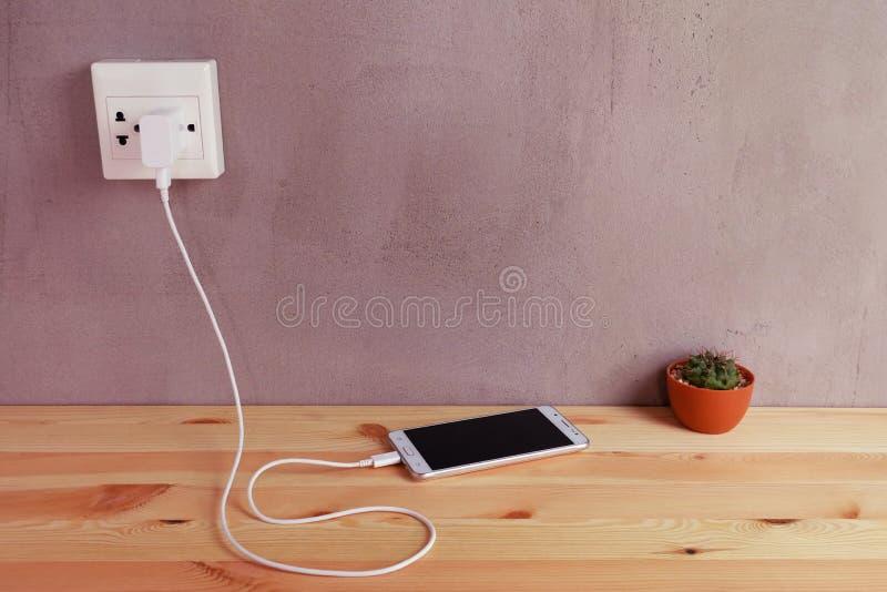 Obstrua dentro o carregador do cabo do adaptador da tomada de poder do telefone celular em de madeira imagem de stock royalty free