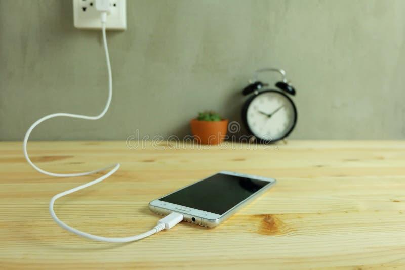 Obstrua dentro o carregador do cabo do adaptador da tomada de poder do telefone celular em de madeira foto de stock