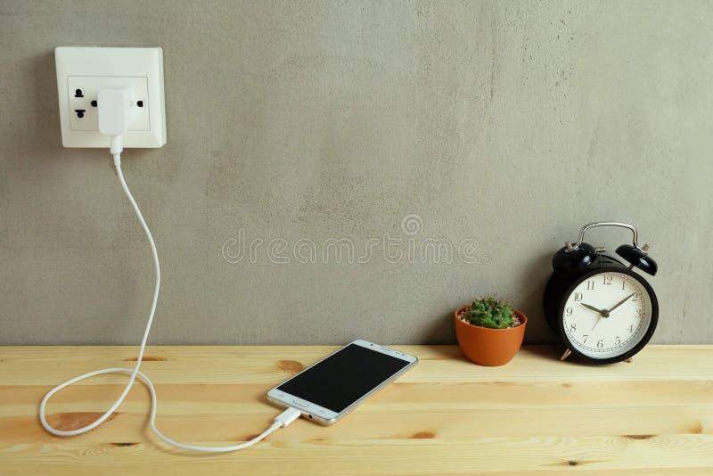 Obstrua dentro o carregador do cabo do adaptador da tomada de poder do telefone celular em de madeira imagem de stock