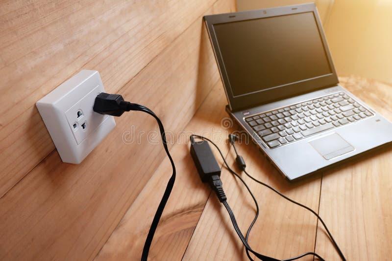 Obstrua dentro o carregador do cabo de alimentação do adaptador do laptop no assoalho de madeira fotografia de stock royalty free